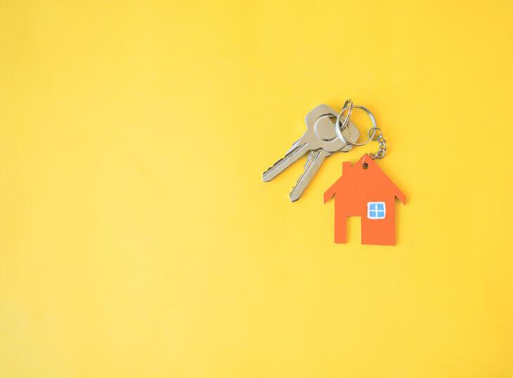 Nøkkel med hus-nøkkelring på gul bakgrunn